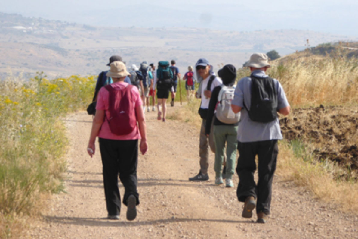 A group of people walking down a dirt road